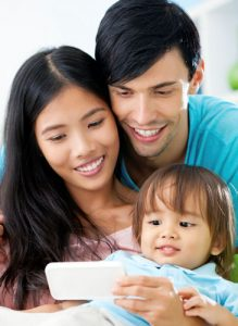 asian family with baby looking at phone